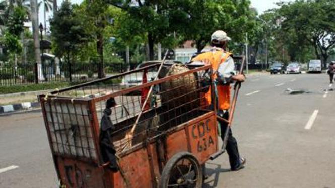 Tukang sampah menyusuri jalan Ibukota