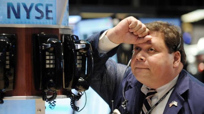 Seorang pialang lemas melihat anjloknya harga saham
