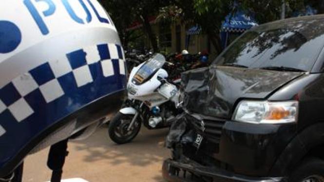 Helm polisi di antara mobil yang rusak akibat tabrakan