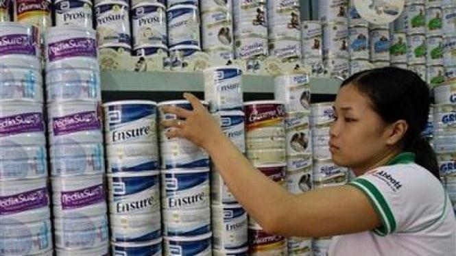Pegawai Toko di Vietnam Memeriksa Stok Susu
