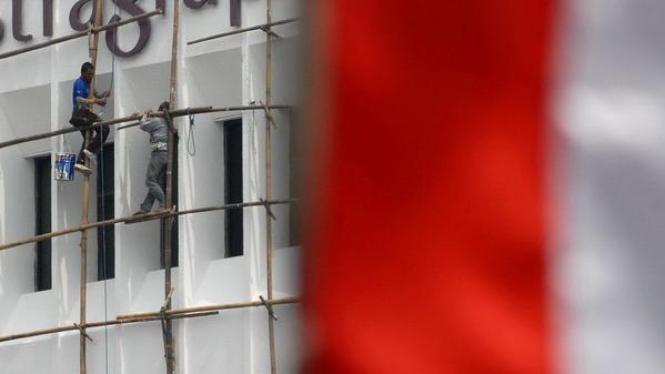 Pekerja sedang mengecat salah satu kantor di Jakarta