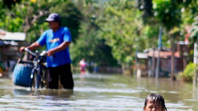 Anak-anak bermain air di saat banjir