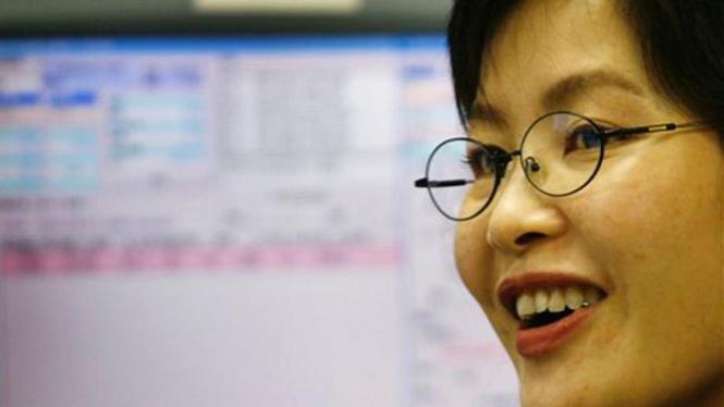 Seorang pialang di Hong Kong tersenyum dengan naiknya harga saham
