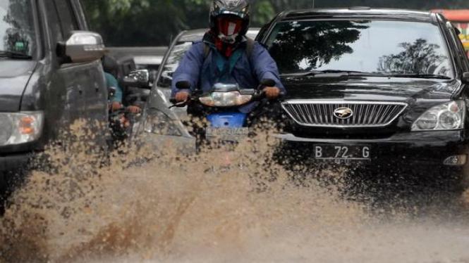 Sejumlah kendaraan menerjang air yang menggenangi Jalan Jendral Sudirman