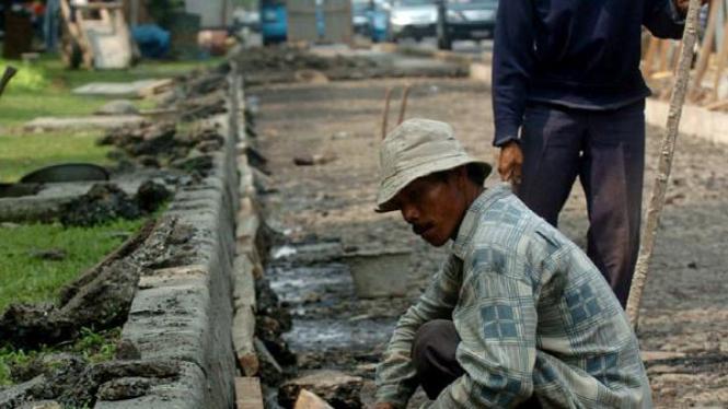 Pekerja memperbaiki jalur Transjakarta koridor I.