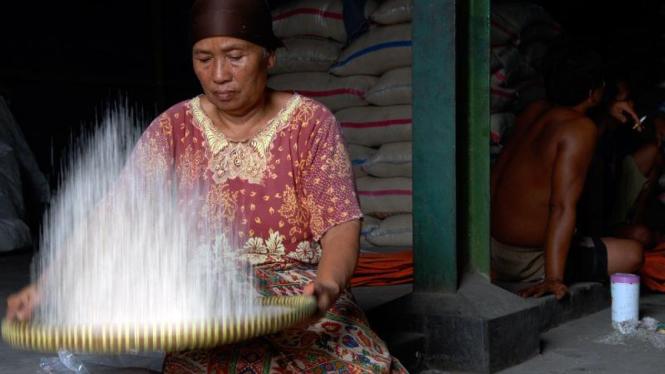 Seorang ibu menampih beras di Pasar Induk Cipinang,Jakarta.