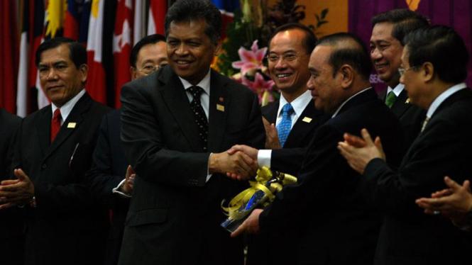 Surin Pitsuwan menyerahkan simbol Piagam ASEAN kepada Mun Patanotai(kanan).