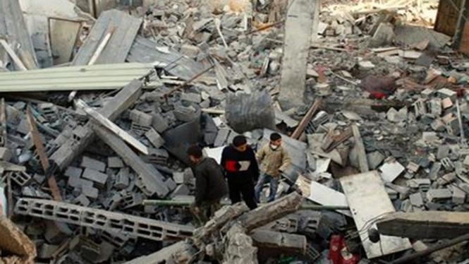 Penduduk Jalur Gaza memandangi reruntuhan bangunan yang dibom Israel