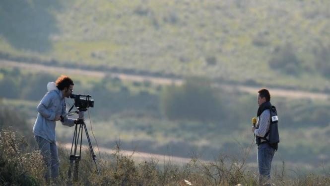 Dua wartawan meliput di suatu bukit dekat perbatasan Israel-Jalur Gaza