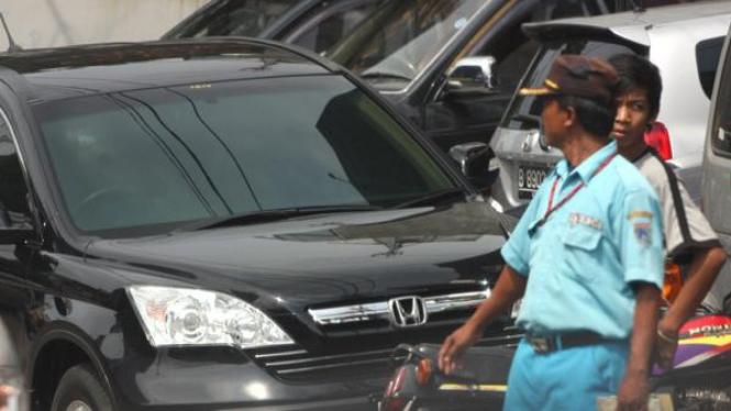 Tukang parkir tengah mengatur di sebuah jalan Jakarta
