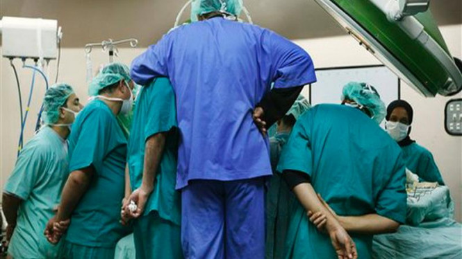 Tim dokter sedang membedah seorang pasien