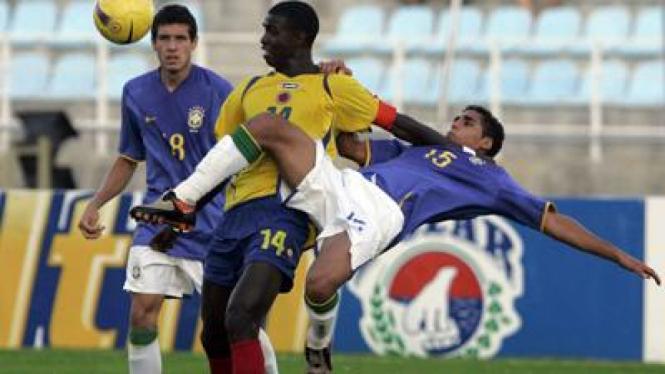 Douglas (kanan) berebut bola dengan pemain Kolombia Marco Perez (kuning)