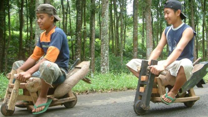 Dua bocah bermain sepeda kayu di hutan Punjul, Puspo, Pasuaruan, Jawa Timur