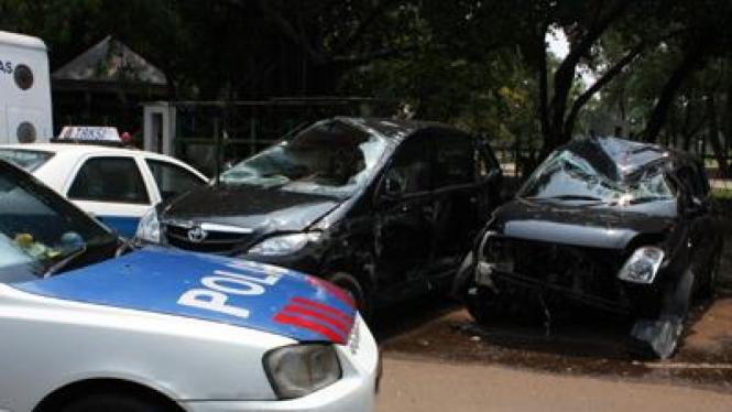 Mobil polisi di antara kendaraan yang rusak
