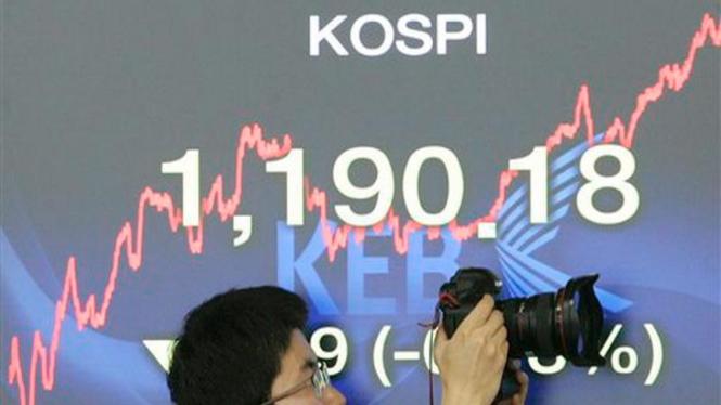 Seorang fotografer mengambil gambar di depan grafik indeks saham di Korsel