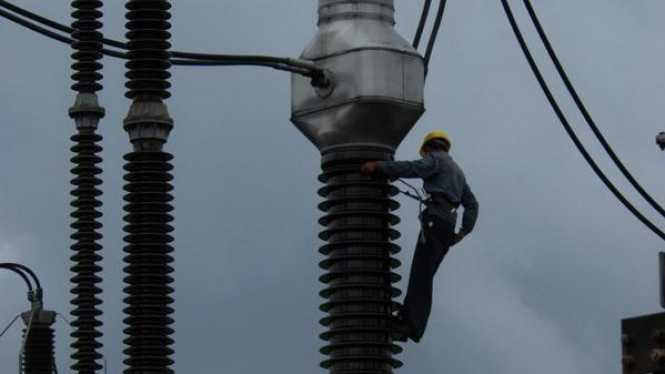 Petugas PLN tengah memperbaiki jaringan listrik di Gardu Induk Gandul, Jakarta.