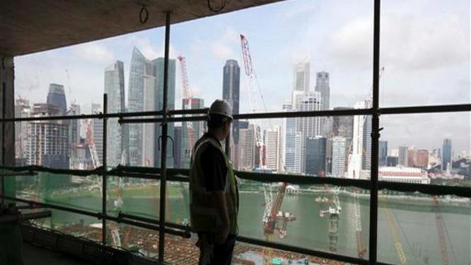 Seorang pekerja memandang gedung-gedung pencakar langit di Singapura