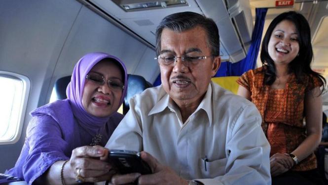 Jusuf Kalla menggunakan Blackberry disaksikan istri dan putrinya