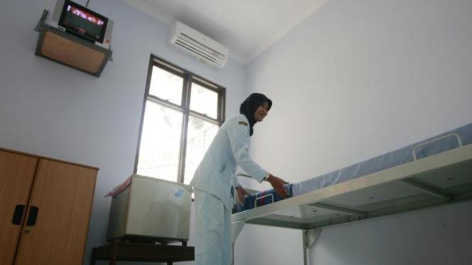 Seorang perawat tengah membereskan ranjang pasien di suatu rumah sakit.