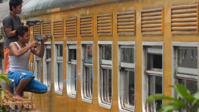 Dua pekerja memoles bagian luar gerbong kereta Gaya Baru di Manggarai, Jakarta.