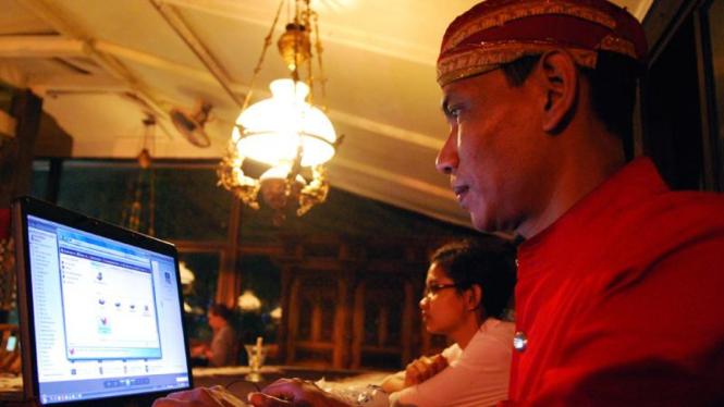 Seorang kasir menggunakan laptop