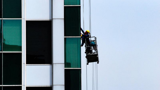 Pekerja membersihkan kaca gedung perkantoran di Jakarta