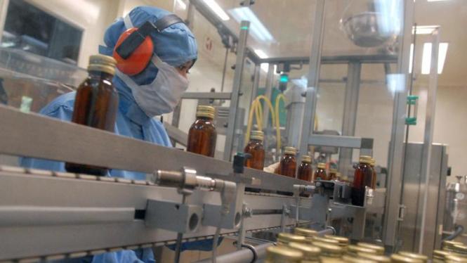 Pekerja pabrik farmasi tengah mengawasi pengemasan obat.