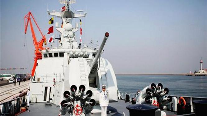 Seorang prajurit menjaga sebuah kapal perang China di Kota Qingdao