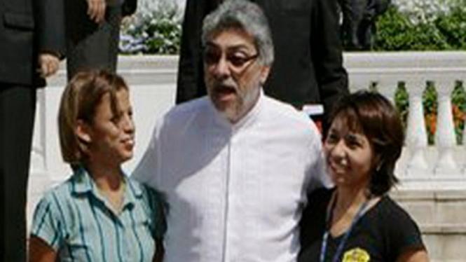 Fernando Lugo (tengah) saat berpose dengan dua wartawati