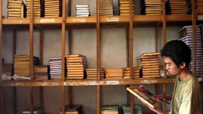 Santri membersihkan koleksi Kitab Kuning Pondok Pesantren Petuk, Kediri