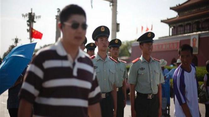 Polisi berpakaian sipil (kiri dan kanan) berjaga di Lapangan Tiananmen, Beijing
