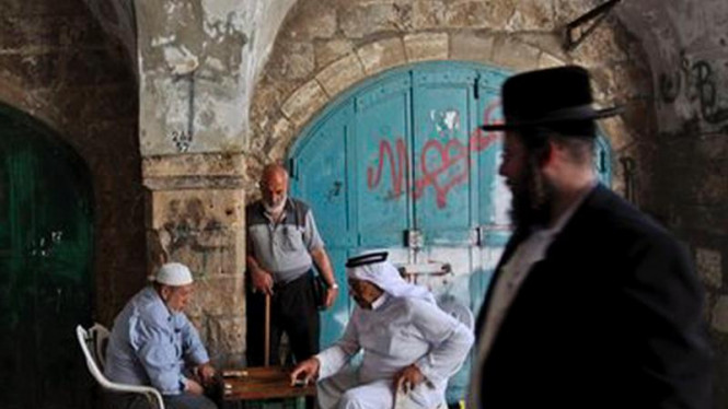 Seorang umat Yahudi menyaksikan umat Muslim bermain catur di Yerusalem