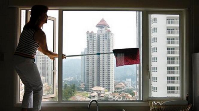 Seorang pembantu membersihkan jendela apartemen di Kuala Lumpur, Malaysia