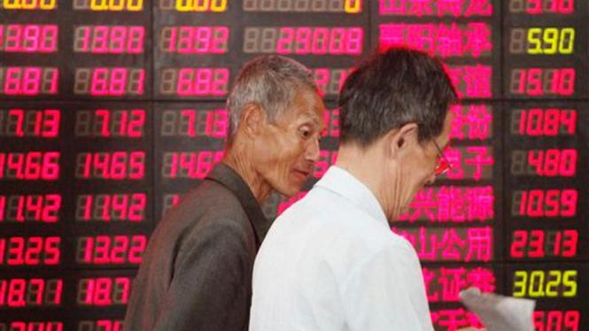 Dua orang investor mengamati harga saham di Shanghai, China