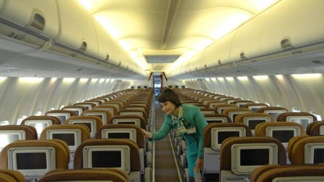 Seorang pramugari melihat kursi Boeing 737-800 NG milik Garuda