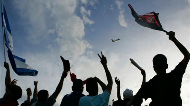 Rakyat Honduras menyaksikan pesawat yang membawa Presiden Manuel Zelaya