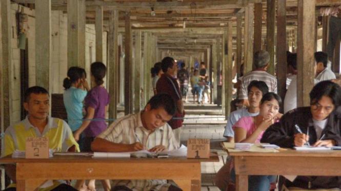 Suku Dayak memilih di TPS di rumah tradisional Betang