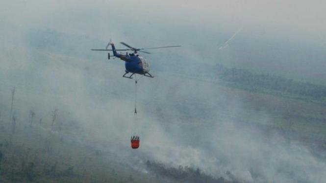 Ilustrasi helikopter menjatuhkan bom air di kebakaran hutan.