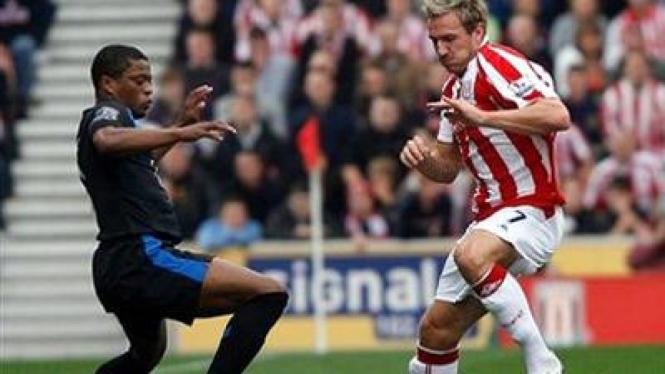 Patrice Evra (kiri) berebut bola dengan pemain Stoke Liam Lawerence