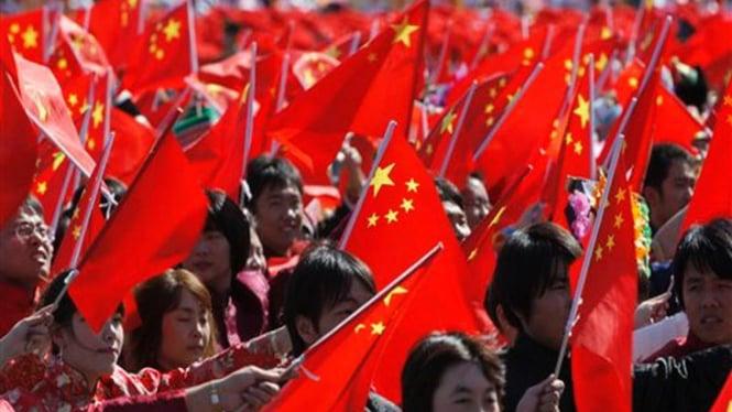 Peserta pawai mengibarkan bendera China di Lapangan Tiananmen, Beijing
