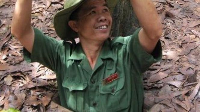 Seorang petugas masuk ke lubang perlindungan Vietcong
