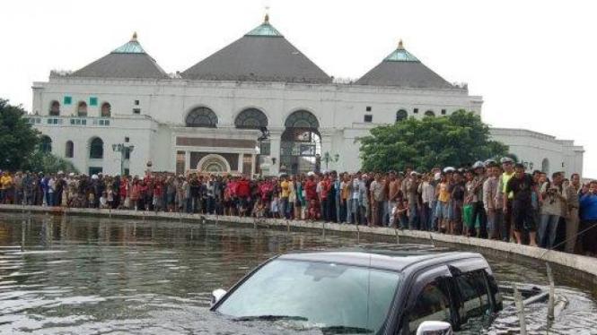 Mobil masuk kolam di depan Masjid Agung Palembang