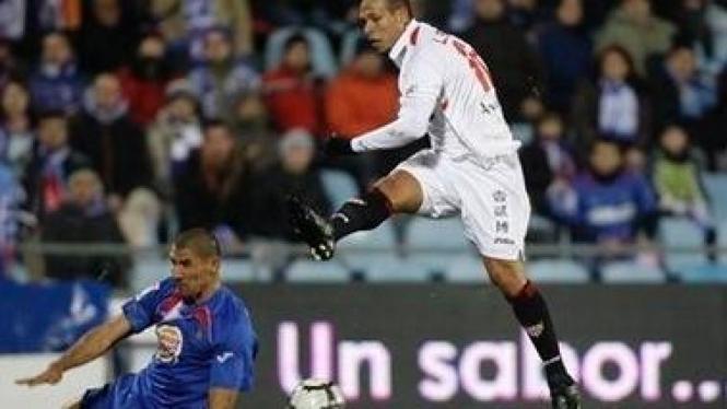 Pemain Sevilla Luis Fabiano (putih) dan pemain Getafe Daniel'Cata Diaz