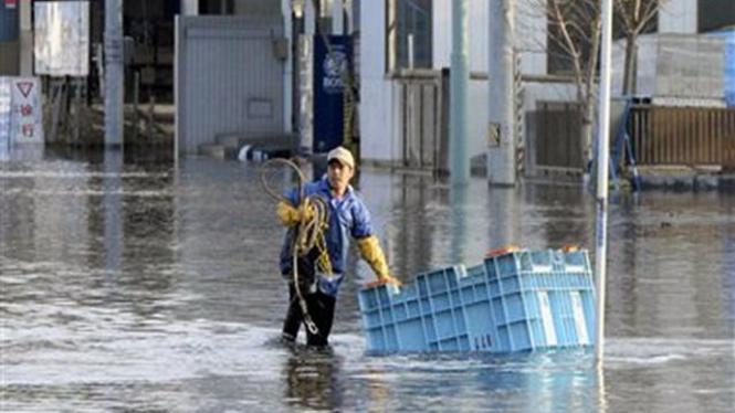 Seorang warga menyusuri banjir akibat tsunami di Kesennuma, Jepang bagian utara