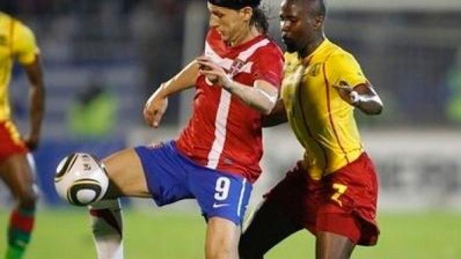 Pemain Serbia Marko Pantelic (merah) dan pemain Kamerun Landry Nguemo