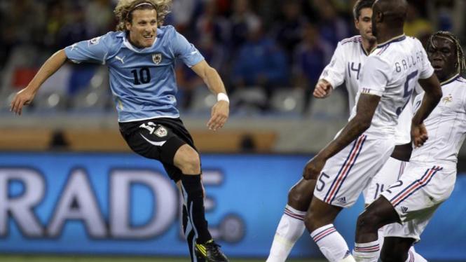 Diego Forlan (kiri) mencoba mengoyak pertahanan Perancis