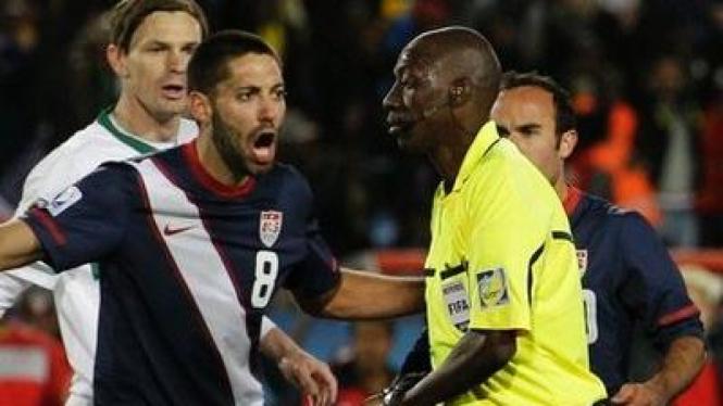 Wasit Koman Coulibaly (kuning) diprotes pemain AS Clint Dempsey (biru)