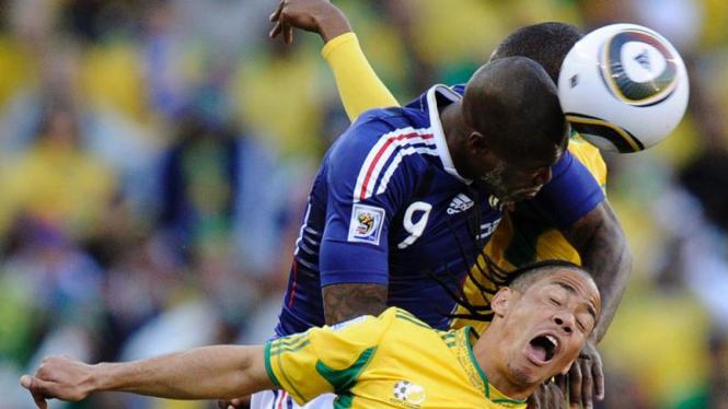 Pemain Prancis, Djibril Cisse berebut bola dengan dua pemain Afrika Selatan.