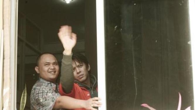 Ariel Peterpan (kanan) melambai lewat jendela tahanan Mabes Polri