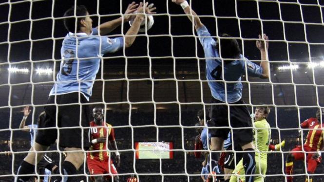 Luis Suarez (kiri) menghalau bola dengan tangannya